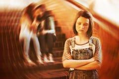 Schoolvrienden die een droevig meisje in schoolgang intimideren stock fotografie