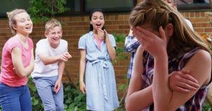 Schoolvrienden die een droevig meisje in schoolgebouw 4k intimideren stock video