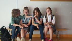 Schoolvriendschap De klasgenoten troosten hun vriend terwijl het zitten op een bank in de schoolgang, terug naar school stock footage
