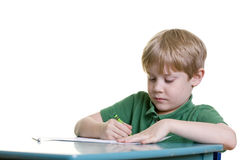 Schoolwork. A child concentrates on his schoolwork stock photo