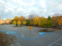 Schoolyard in autumn. Schoolyard with maple trees and basketball hoop in autumn Royalty Free Stock Photography