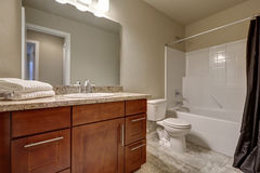 Schoon en warm badkamersbinnenland met tegelvloer en beige muren Stock Afbeelding