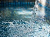 Schoon lopend water in pool met blauwe kleur stock afbeelding