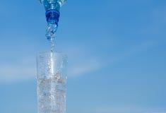 Schoon zuiver water die onderaan het bespatten van een fles in een duidelijk glas worden gegoten Royalty-vrije Stock Fotografie