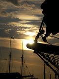 Schooner. The sun is setting behind the bowsprit of an old schooner stock image