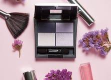 Schoonheid, decoratieve schoonheidsmiddelen en giftdoos met boog De make-upborstels plaatsen en kleuren oogschaduwpalet op helder Royalty-vrije Stock Fotografie