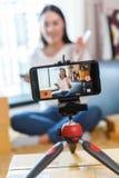 Schoonheid die blogger producten op levende uitzending de aantonen omhoog te maken en te herzien gebruikt smartphone stock fotografie