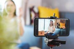 Schoonheid die blogger producten op levende uitzending de aantonen omhoog te maken en te herzien gebruikt smartphone stock foto's