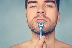 Schoonheid en gezondheidszorgconcept Mens met varkenshaar op blauwe achtergrond Macho het scheren kin met scheermes Kerel die met stock afbeeldingen