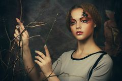 Schoonheid en kunstconcept: De jonge vrouw met helder maakt omhoog met droge takken Stock Foto's