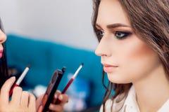 Schoonheid en make-upconcept - close-upportret die van mooie vrouw professionele samenstelling met borstel krijgen Stock Fotografie