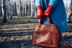 Schoonheid en manier Modieuze modieuze vrouw die heldere kleding draagt die bruine zakhandtas houdt stock fotografie