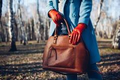 Schoonheid en manier Modieuze modieuze vrouw die heldere kleding draagt die bruine zakhandtas houdt stock foto