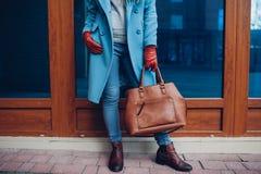 Schoonheid en manier Modieuze modieuze vrouw die laag en handschoenen dragen, die bruine zakhandtas houden stock foto's