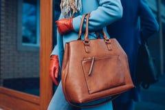 Schoonheid en manier Modieuze modieuze vrouw die laag en handschoenen dragen, die bruine zakhandtas houden stock afbeelding