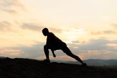 Schoonheid en sportenconcept Silhouet van bodybuilder het stellen bij zonsondergang tijdens zijn openlucht opleiding royalty-vrije stock foto