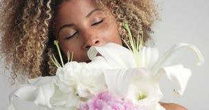 Schoonheid gemengde rasvrouw in studio met bloemen stock video
