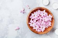 Schoonheid, kuuroord en wellnesssamenstelling van geparfumeerd roze bloemenwater in houten kom en kaarsen op steenlijst Aromather stock afbeeldingen