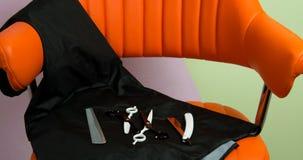 In schoonheid ligt de salon op de oranje stoel hulpmiddelen voor kapsels, schaar, en voor het scheren van scheermesje stock afbeeldingen