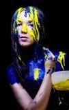 Schoonheid/manier schilderde het dichte omhooggaande portret van vrouw blauw en geel met borstels en verf op zwarte achtergrond Stock Afbeelding
