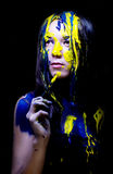 Schoonheid/manier schilderde het dichte omhooggaande portret van vrouw blauw en geel met borstels en verf op zwarte achtergrond Royalty-vrije Stock Fotografie