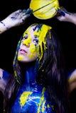 Schoonheid/manier schilderde het dichte omhooggaande portret van vrouw blauw en geel met borstels en verf op zwarte achtergrond Royalty-vrije Stock Afbeelding