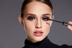 schoonheid Mooie Vrouw die Zwarte Mascara op Wimpers toepassen stock afbeeldingen
