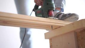 Schoonheid van langzame motie in bouw en reparatie - mens die een houten raad met een elektrische figuurzaagclose-up zagen stock video
