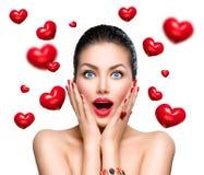 Schoonheid verraste vrouw met vliegende rode harten Royalty-vrije Stock Afbeelding