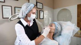 Schoonheid vrouwelijke arts in gezondheidszorgkliniek de procedure van de lippenmodulatie lippenvergroting met injecties 4K stock videobeelden