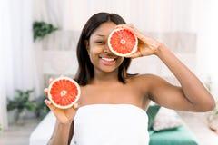 Schoonheids Afrikaanse vrouw met oranje citrusvruchtengrapefruit met gezond huidlichaam Aantrekkelijke verse vitamine Het schot v royalty-vrije stock afbeelding
