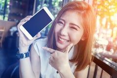 Schoonheids Aziatisch meisje die en smartphone glimlachen tonen royalty-vrije stock afbeelding