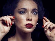 Schoonheids donkerbruine vrouw onder zwarte sluier met rode manicure dichte omhooggaand, treurend weduwe, Halloween-make-up Stock Foto's