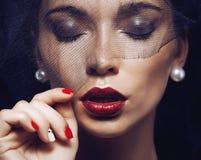 Schoonheids donkerbruine vrouw onder zwarte sluier met rood Royalty-vrije Stock Foto