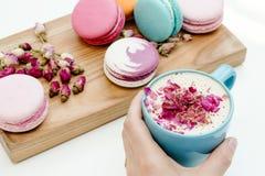 Schoonheids Franse macarons die op houten bureau en hand blauwe kop van cappuccino op witte lijst houden als achtergrond Royalty-vrije Stock Afbeeldingen