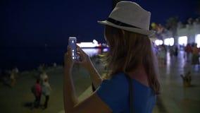 Schoonheids gelukkig jong meisje die beeld van mooie nachtstad nemen op slimme telefoon stock video