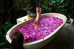 Schoonheids het jonge Vrouw ontspannen in openluchtbad met tropische bloem stock foto