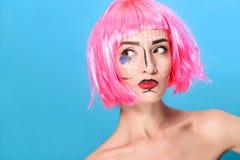 Schoonheids hoofdschot De jonge vrouw met creatief pop-art maakt omhooggaande en roze pruik bekijkend de camera op blauwe achterg Stock Foto