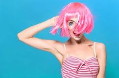 Schoonheids hoofdschot De jonge vrouw met creatief pop-art maakt omhooggaande en roze pruik bekijkend de camera op blauwe achterg Stock Afbeelding