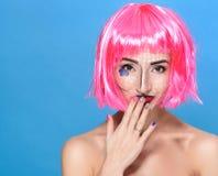 Schoonheids hoofdschot De leuke Jonge vrouw met creatief pop-art maakt omhooggaande en roze pruik bekijkend de camera op blauwe a Stock Afbeelding