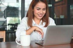 Schoonheids jonge Aziatische bedrijfsvrouw met laptop die in modern bureau werken royalty-vrije stock afbeelding