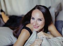Schoonheids jonge donkerbruine vrouw in het binnenland van het luxehuis, grijze modieus van de feeslaapkamer Royalty-vrije Stock Afbeeldingen