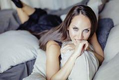 Schoonheids jonge donkerbruine vrouw in het binnenland van het luxehuis, grijze modieus van de feeslaapkamer Stock Afbeeldingen