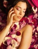 Schoonheids jonge donkerbruine vrouw met bloem dichte omhooggaand Stock Foto