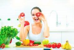 Schoonheids jonge grappige vrouw die verse groenten in haar keuken thuis houden stock foto
