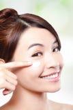 Schoonheids jonge vrouw die kosmetische room toepassen Stock Foto