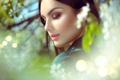 Schoonheids jonge vrouw die van aard in de boomgaard van de de lenteappel, Gelukkig mooi meisje in een tuin met bloeiende fruitbo stock foto's