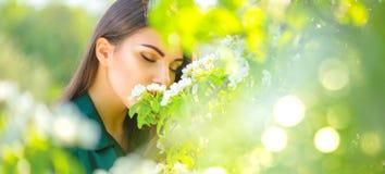 Schoonheids jonge vrouw die van aard in de boomgaard van de de lenteappel, Gelukkig mooi meisje in een tuin met bloeiende fruitbo stock afbeelding