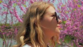 Schoonheids jonge vrouw die in zonnebril in bloeiend park lopen Concept de lenteinspiratie Vrij het vrouwelijke persoon rusten stock video