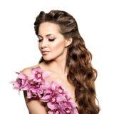 Schoonheids jonge vrouw, luxe lang krullend haar met orchideebloem H Royalty-vrije Stock Foto
